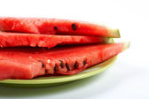 Watermelon slices on the green plate — Stock Photo