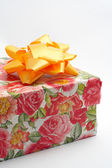 Gift box with yellow ribbon, detail on white background — Stock Photo