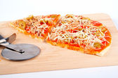 Detail of slices Italian pizza and cutter — Stock Photo