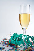 Champagne glass, ribbons and confetti — Stock Photo