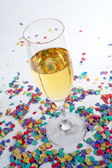 Champagne glass and confetti — Stock Photo