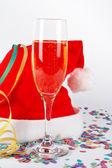 Champán cristal y navidad sombrero, con cintas, confeti — Foto de Stock