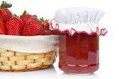 Jam jar and basket of strawberries — Stock Photo