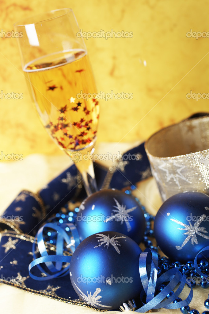 Christmas decoration with champagne bottle and full glass over colour background. Shallow depth of field — Stock Photo #6340188