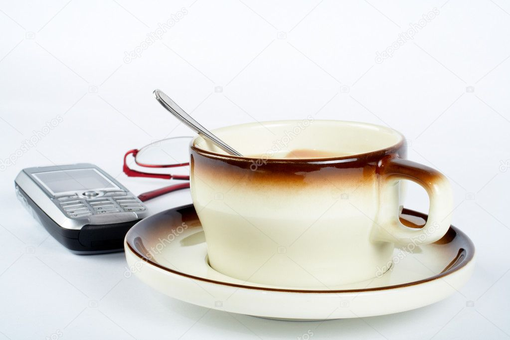 Close-up of a cup of coffee with the spoon inside, cellular phone and pair of glasses on white background — Stock Photo #6347652