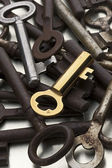 A golden key amid rusty ones — Stock Photo