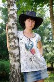 Beautiful girl in the hat around birch — Stock Photo