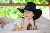 Beautiful girl in the hat lying in the open air — Stock Photo