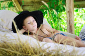 Boy in a cowboy hat is in the hayloft — Stock Photo