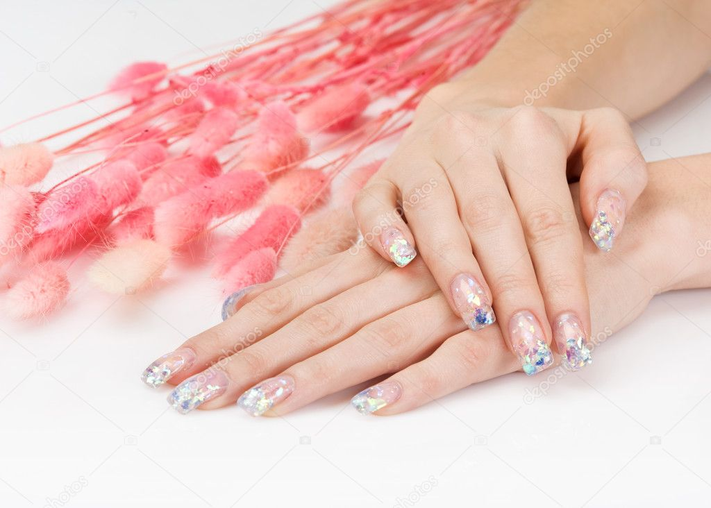 Woman hands with glitter manicure lying down near pink decor spikes — Stock Photo #5756864