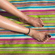 Woman legs on striped towel — Stock Photo