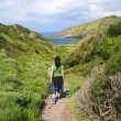Woman hiking towards sea — Foto Stock