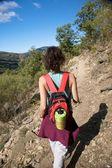 Czerwony plecak kobieta idąc w góry — Zdjęcie stockowe