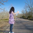 Dark-haired woman hitchhiking — Stock Photo
