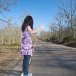 Dark-haired woman hitchhiking — Stock Photo