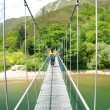 Walking on footbridge over river — Stock Photo