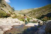 žena krok na skále u řeky — Stock fotografie