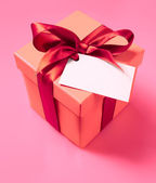 Gift box with ribbon and empty label — Stock Photo