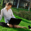 Woman lying on grass with laptop — Stock Photo #6228193