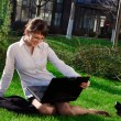 Woman lying on grass with laptop — Stock Photo #6228599