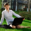 Stock Photo: Woman lying on grass with laptop