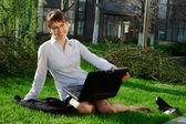Woman lying on grass with laptop — Stock Photo