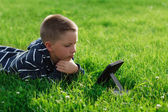 Kid reading an ebook in a park — Stock Photo