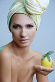 Beautiful woman in yellow scarf on her head and lemon in the hand — Stock Photo