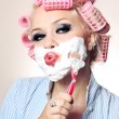 Attractive girl is shaving face - Stock Photo