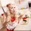 Stock Photo: Desperate housewife holding kitchen knife