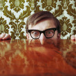 Scared nerd hidding behind a desk - Stockfoto