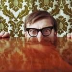 Scared nerd hidding behind a desk — Stock Photo