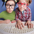 Twin sisters at the computer — Stockfoto