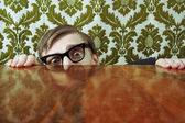 Funny nerd hiding behind a desk — Stock Photo