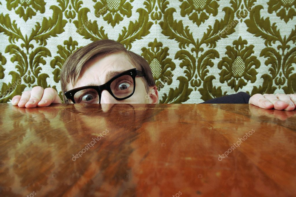 Funny nerd hiding behind a desk  Stock Photo #5821555