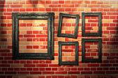 Quadros vintage em uma parede de tijolo — Fotografia Stock