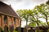 Old cemetery with church and tombstones — Stock Photo