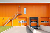 Orange building with loading dock and fire escape stair — Stock Photo
