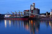 Grain elevators & cargo ship at dusk. — Stock Photo