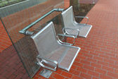 Stainless steel chairs at a bus stop. — Stock Photo
