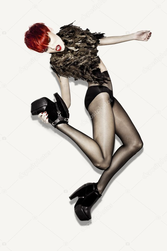 High-End Fashion Model with red hair and feathers jumping in studio on white background. — Stock Photo #5779733