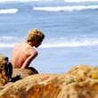 Boy on Rocks at the Beach - Stock Photo