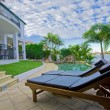 Stock Photo: Deck chairs by the pool at waterfront mansion
