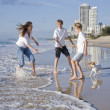 Family playing with dog on the beach — Stock Photo #5788396