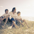 Family sitting on the beach — Stock Photo #5788632
