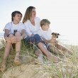 Family sitting on the beach — Stock Photo
