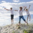 Mum and sons jumping of a sand dune at the beach — Stock Photo #5788795
