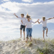 Mum and sons jumping of a sand dune at the beach — Stock Photo