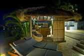 Resort style living with Bali hut with bar and deck chairs — Stock Photo
