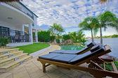 Solstolar vid poolen på waterfront mansion — Stockfoto